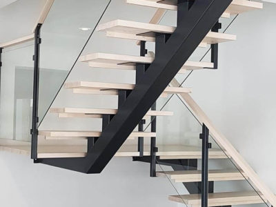 Staircase with glass railings on steel beam.